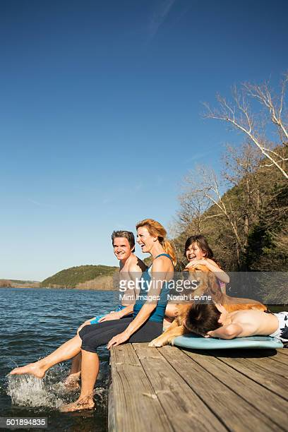 a family and their retriever dog on a jetty by a lake. - one animal stock pictures, royalty-free photos & images