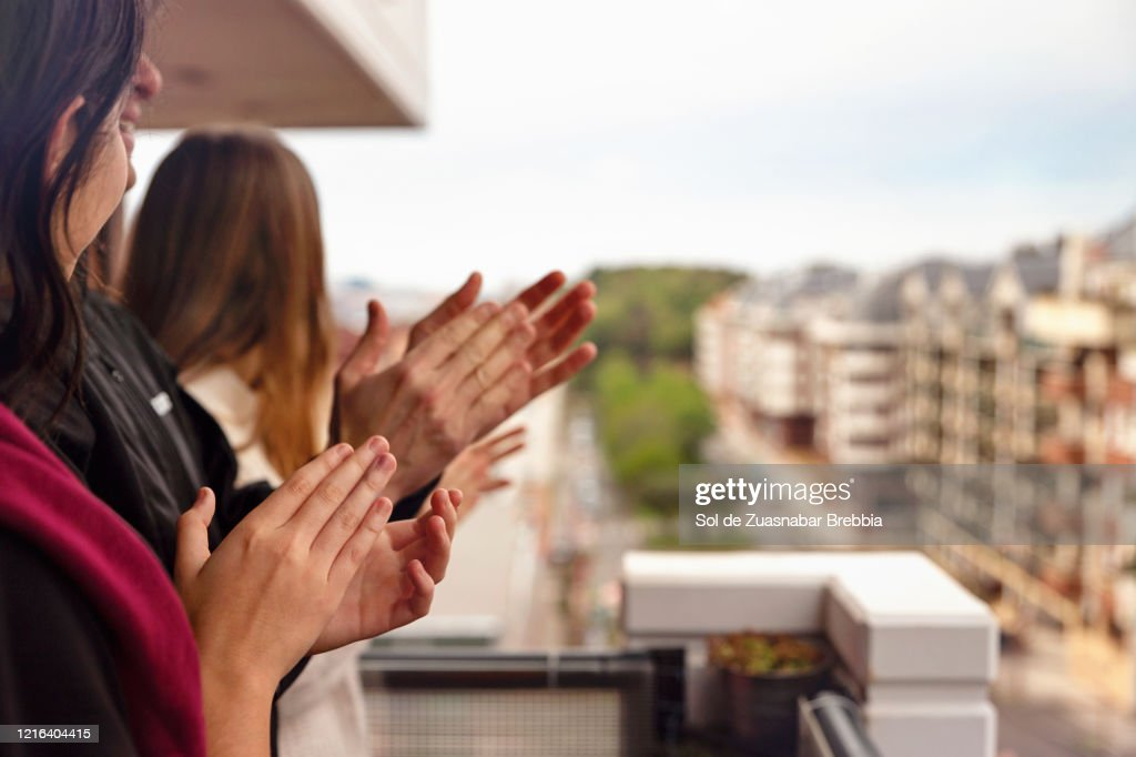 Family applauding from the balcony of their home : Stock-Foto