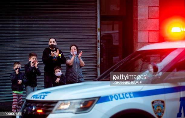 Family applauds in front of the Mount Sinai Hospital in Queens next to a police car to show gratitude to medical staff and essential workers working...