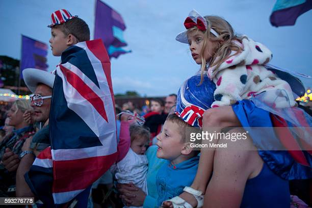 A family are dressed up in their special Union Jack patriotic regalia as they watch the opening ceremony of the 2012 Olympic Games on a big screen at...