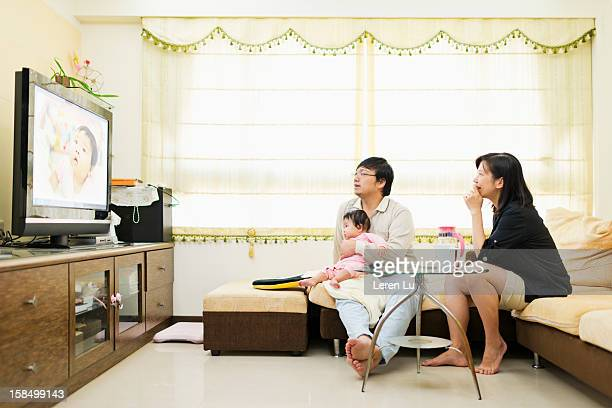 Family are looking at TV in living room