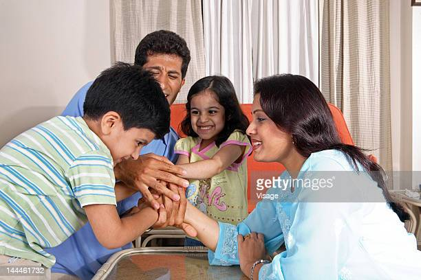 A family arm wrestling playfully