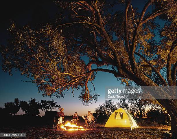 family around camp fire, night (digital composite) - campfire stock pictures, royalty-free photos & images