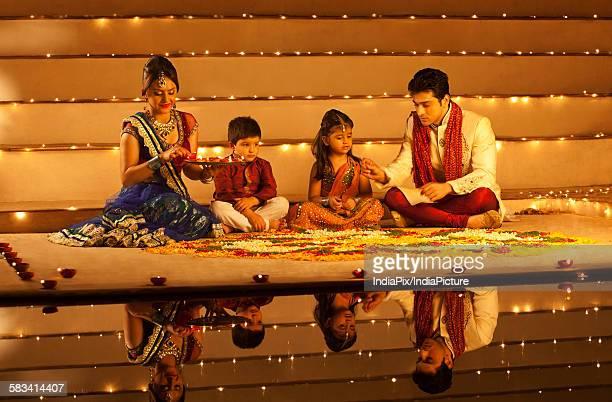 Family arranging diyas on rangoli