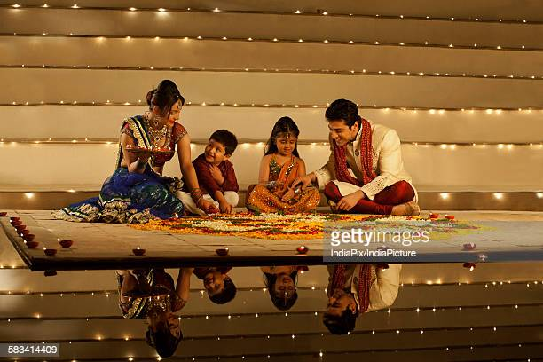 Family arranging diyas on rangoli