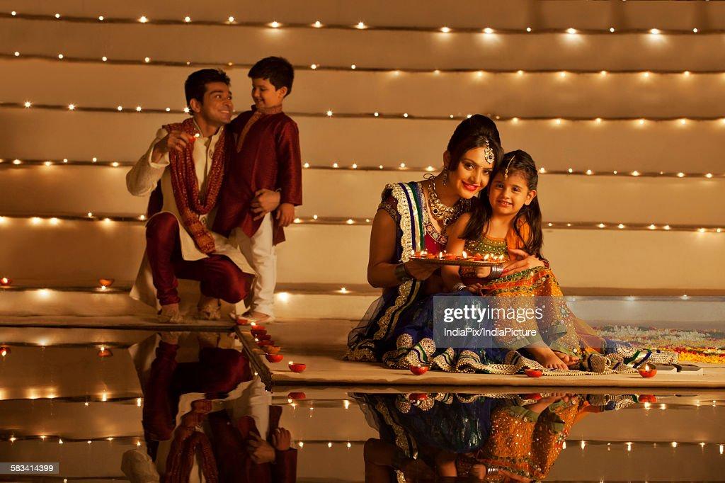 Family arranging diyas : Stock Photo
