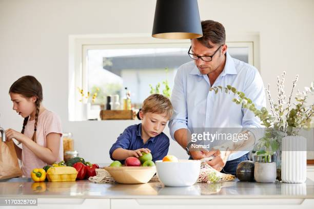 family arranging groceries at kitchen island - danish food stock pictures, royalty-free photos & images