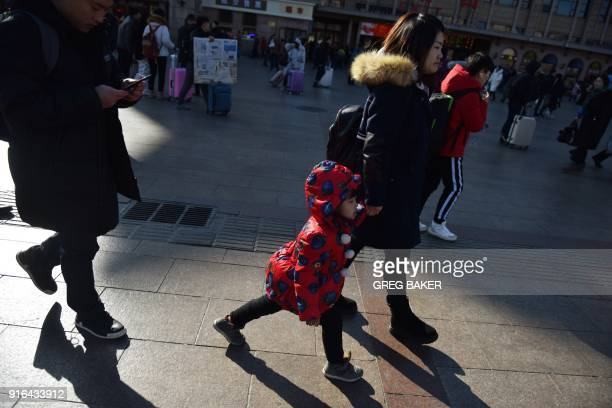 A family arrive at a railway station in Beijing on February 10 as travellers depart the capital ahead of the Lunar New Year China is in the midst of...