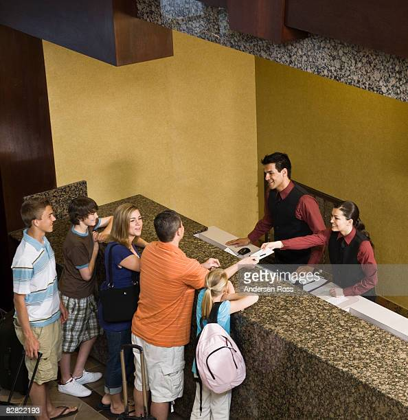 Family arrive at hotel and greeted by hotel staff
