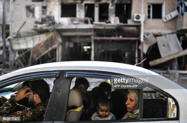 A family arrives to check on their house in Raqa on October 20 after a Kurdishled force expelled the Islamic State group from the northern Syrian...