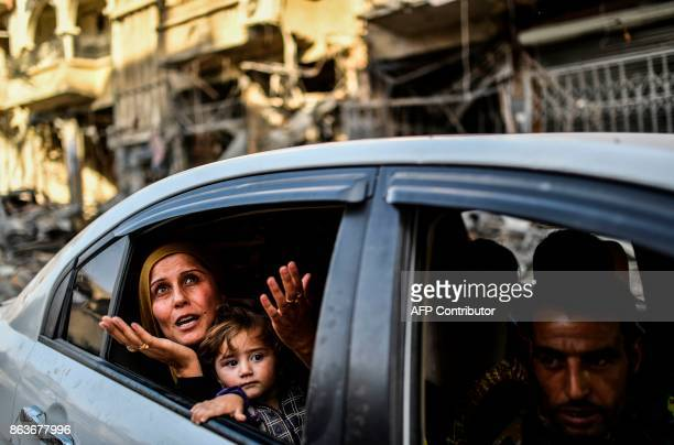 TOPSHOT A family arrives to check on their house in Raqa on October 20 after a Kurdishled force expelled the Islamic State group from the northern...