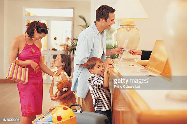 Family Arriving at a Hotel Reception Desk