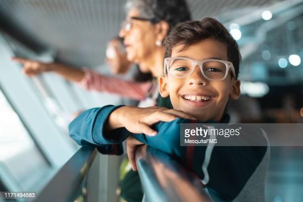 família no terminal de aeroporto que presta atenção aos aviões descolar - spectacles - fotografias e filmes do acervo