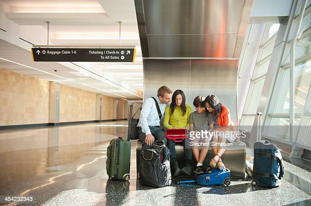family at airport using technology
