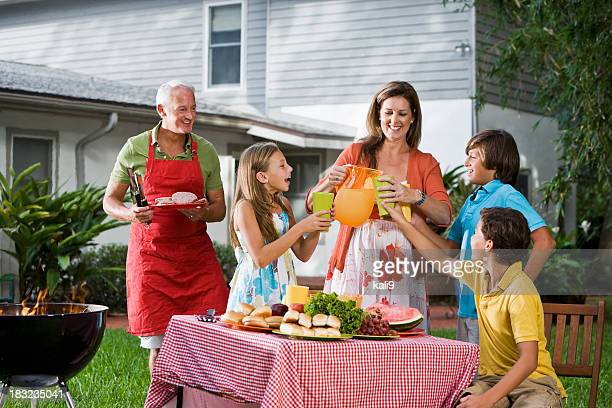 Family at backyard picnic table pouring lemonade