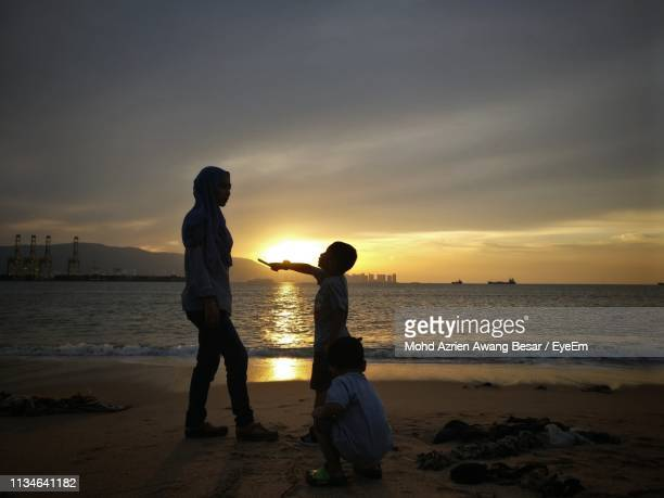 Family At Beach Against Sky During Sunset