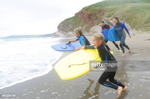 family at beach body boarding - surf stock pictures, royalty-free photos & images