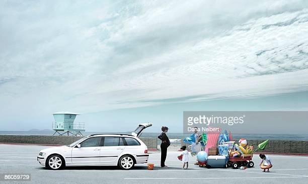 Family at beach loading station wagon