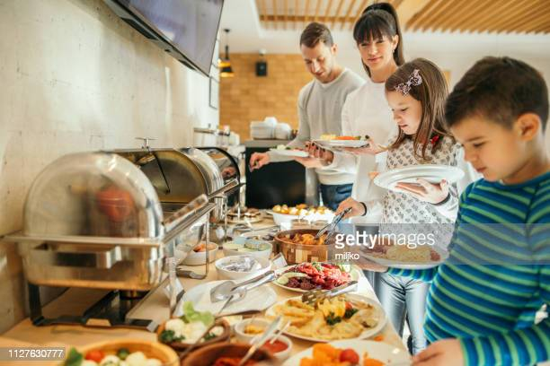 family at breakfast in hotel restaurant - hotel breakfast stock pictures, royalty-free photos & images