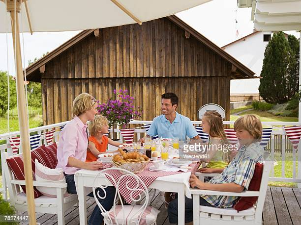 Parents with children (8-13) sitting at breakfast table