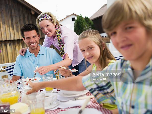Parents with children (10-13) sitting at breakfast table, smiling, portrait