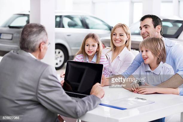 Family at car dealership.