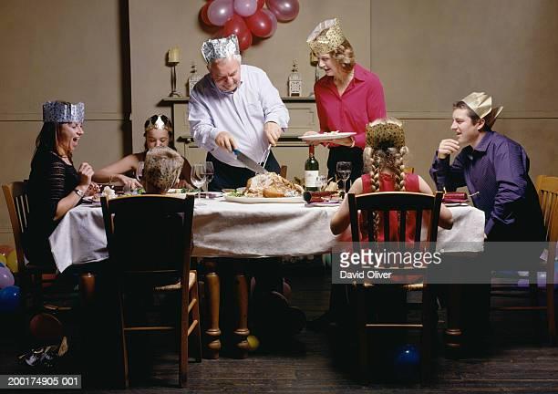 Family at christmas dinner table, senior man carving turkey