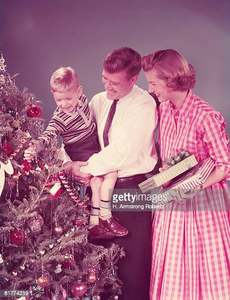 Family at Christmas, mother holding presents, father carrying son. (Photo by H. Armstrong Roberts/Retrofile/Getty Images)
