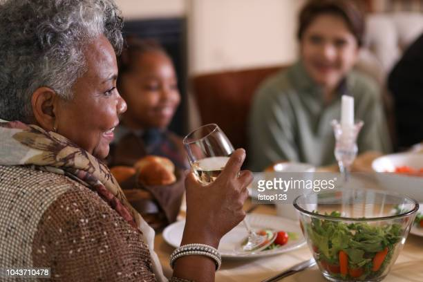 family at dining table eating thanksgiving dinner. - black family dinner stock photos and pictures