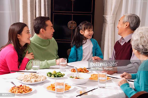 Family at dinner table having traditional food, girl standing next to grandfather
