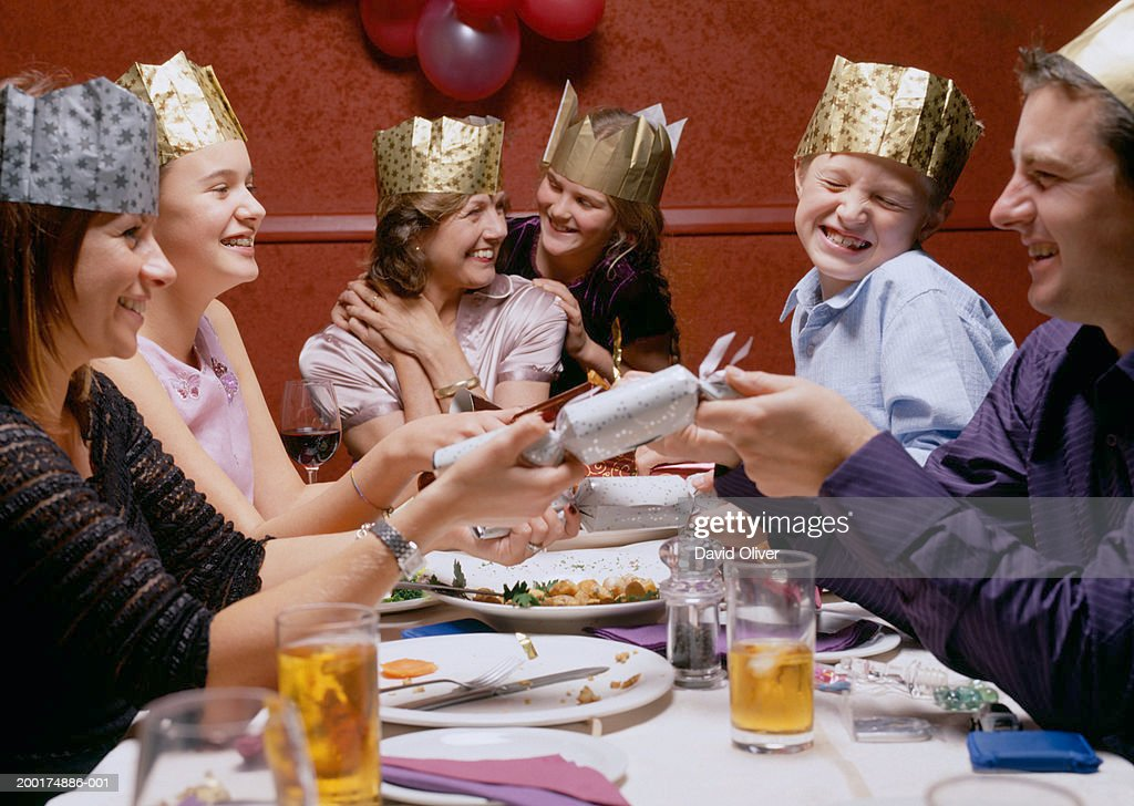 Family At Dinner Table Wearing Party Hats Opening