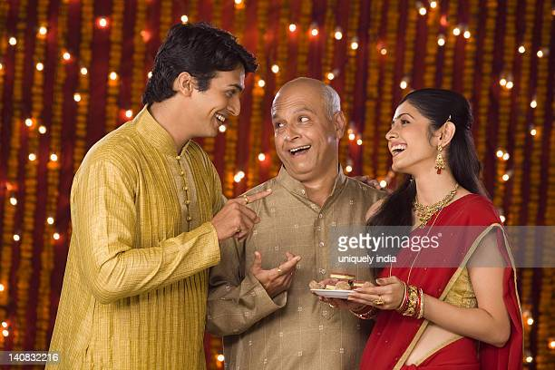 family at diwali occasion smiling and holding a plate full of sweets - sweet food stock pictures, royalty-free photos & images