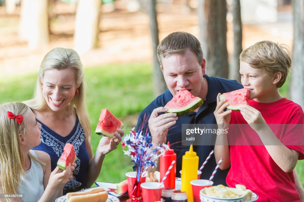 Family at fourth of July cookout eating watermelon : Stock Photo