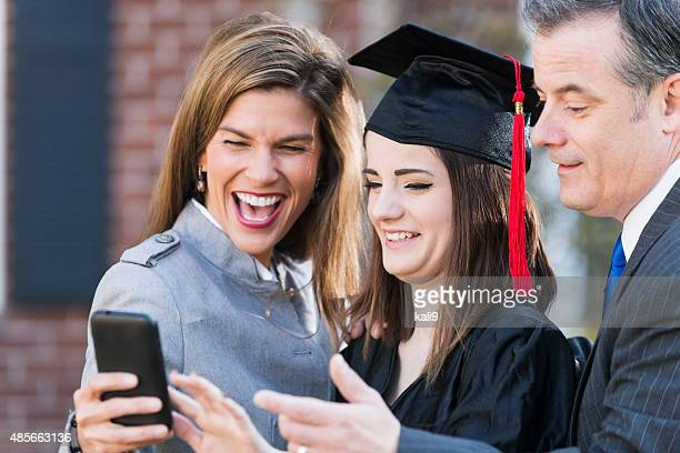 Family at graduation looking at mobile phone