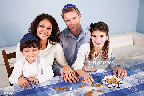 Família em Hanukkah com dreidl e Moeda