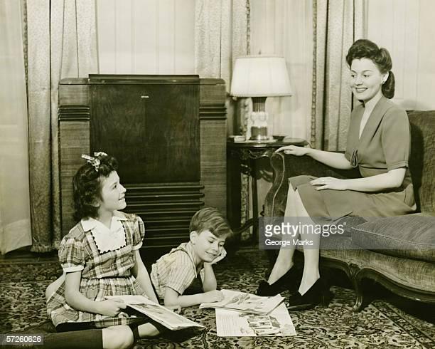 Famiglia a casa, bambini (6-7) (10-11) Riproduzione sul tappeto, madre