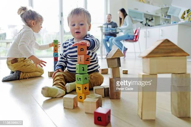 family at home, children playing with building blocks - preparation stock pictures, royalty-free photos & images