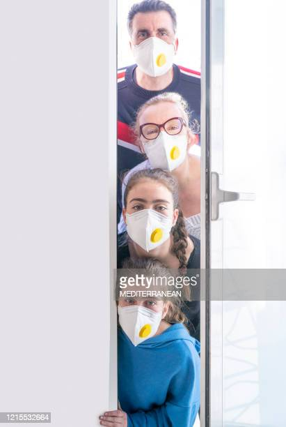 family at home door in coronavirus quarantine humor looking out - funny surgical masks stock pictures, royalty-free photos & images