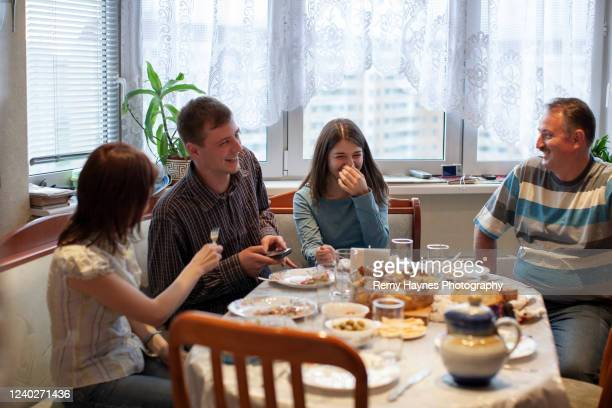 family at home laughing around the dinner table - russia stock pictures, royalty-free photos & images