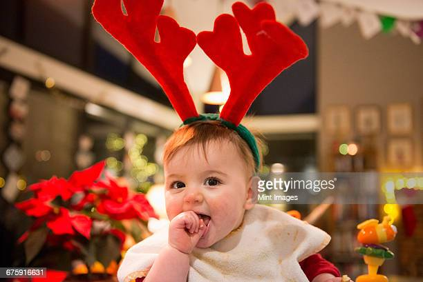 A family at home on Christmas Day. A baby girl wearing felt antlers.
