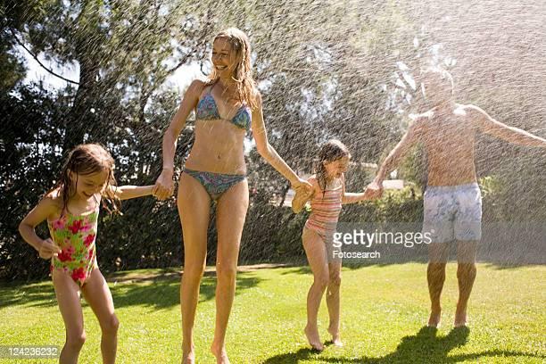 family at home playing in garden - fille sous la douche photos et images de collection