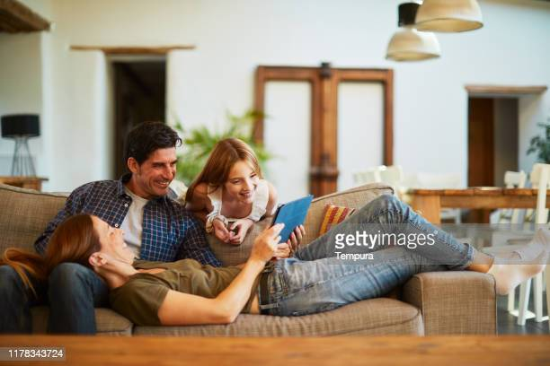 family at home sharing a digital tablet and relaxing on the sofa. - family at home stock pictures, royalty-free photos & images