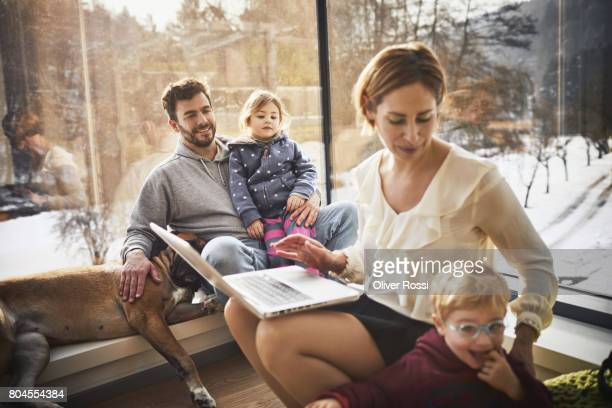 family at home with mother using laptop - stubble stock pictures, royalty-free photos & images