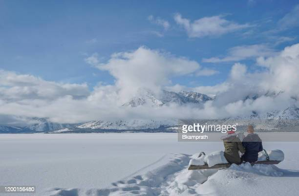 family at jackson lake in the winter at christmas in the grand tetons national park and yellowstone national park usa - jackson hole stock pictures, royalty-free photos & images