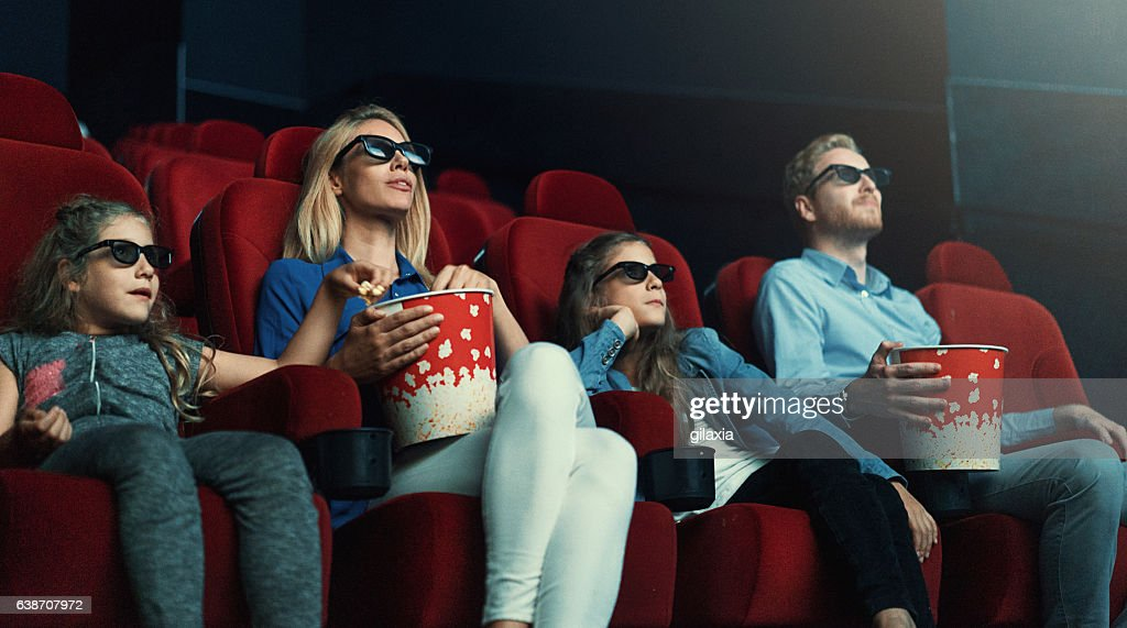 Family at movie theatre. : Stock Photo