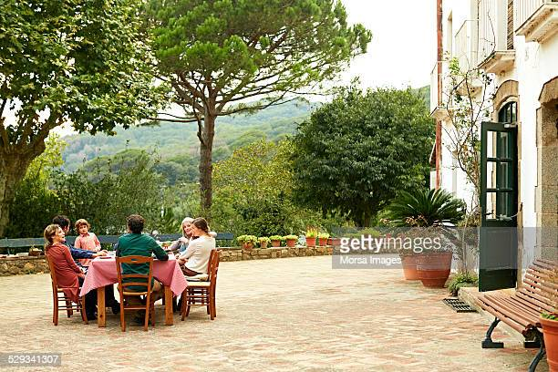 Family at outdoor meal table in yard