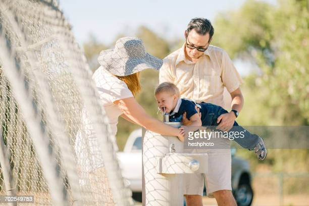 family at playground, father holding young son over water fountain - heshphoto stockfoto's en -beelden