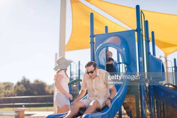 family at playground, father sliding down slide - heshphoto stockfoto's en -beelden