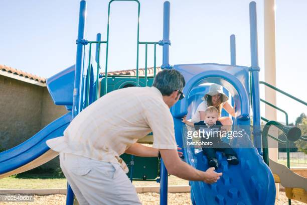 family at playground, young son sliding down slide - heshphoto - fotografias e filmes do acervo