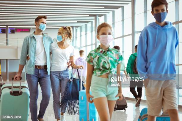 family at the airport with luggage, wearing n95 face masks - izusek stock pictures, royalty-free photos & images